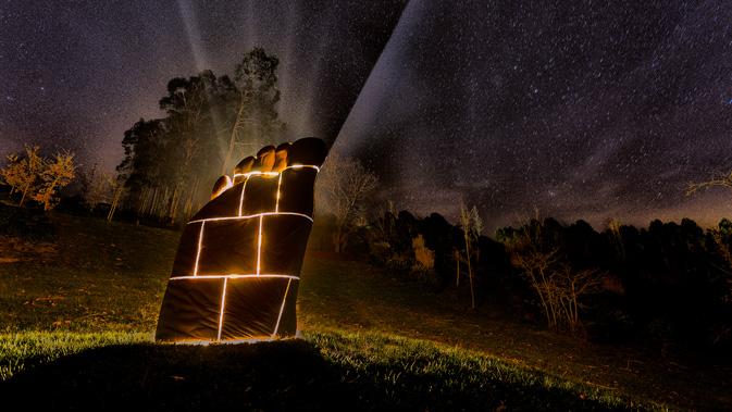 vista nocturna de la escultura con madera sostenible
